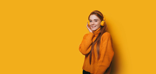 Portrait of cute young woman with red hair and freckles looking at camera smiling while listening music on yellow head phones against yellow wall.