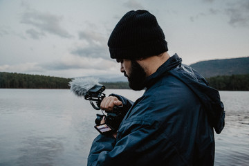 Side view of serious man in warm clothes reviewing photos on camera standing on beach of lake on cloudy day