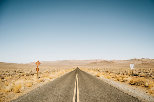 Empty straight road with traffic signs in desert of USA on sunny day
