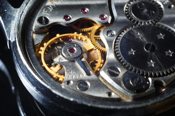 Old wrist watch with metal gears and cogwheels. Detail of watch machinery, macro.