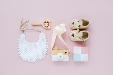 Cute shoes, bib and wooden toys. Set of baby stuff and accessories for girl on pastel pink background.  Baby shower concept.  Fashion newborn. Flat lay, top view