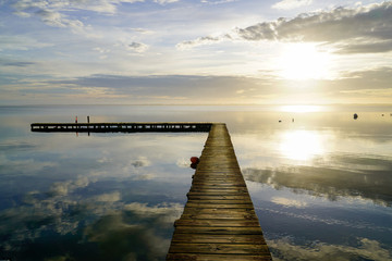 sunrise wood pontoon in water reflection sunset sun in lake mirror image