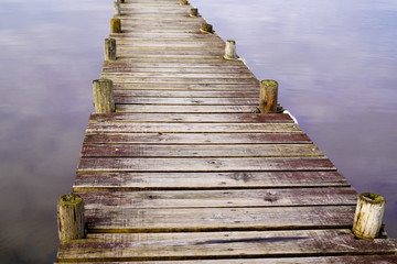 wooden detail background pontoon on water lake with mirror image of sky