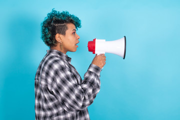 african american girl or woman with megaphone isolated on blue background