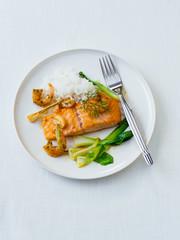 Lachsfilet mit Gemüse und Garnelen auf Teller freigestellt auf weißem untergrund
