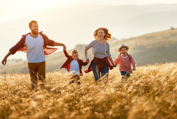 Happy family: mother, father, children son and daughter runing and jumping on sunset.