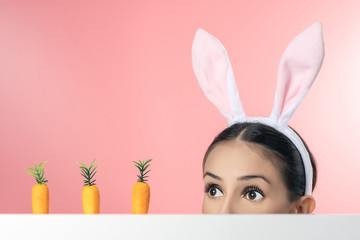 Beautiful young woman with pink bunny ears and toy carrot on pink background. Minimal Easter concept.