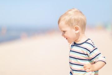 Little cheerful boy on the beach on a sunny summer day