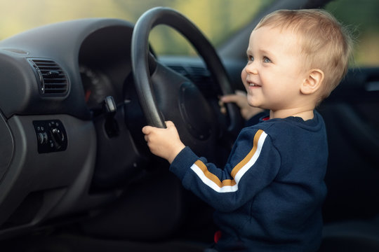 Cute little boy pretending to drive a car sitting behind the steering wheel