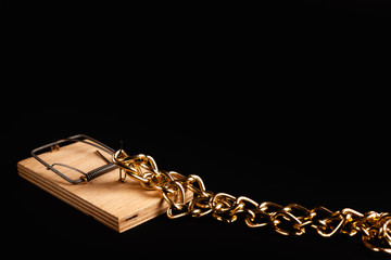 Gold chain in a mousetrap. Concept photo of a bait for greedy. Protection of values.