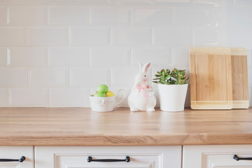 Easter Eggs, Rabbit, Cutting Boards, Succulent On The Kitchen Counter. Bright And Clean Rustic Kitchen With White Cabinets, Close Up. Kitchenware In Modern Kitchen Interior. White Tiles