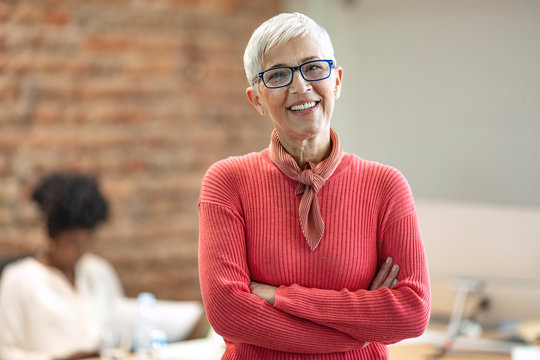 Pretty older business woman, successful confidence with arms crossed in financial building. Cheerful attractive businesswoman crossing arms on chest and looking at camera.