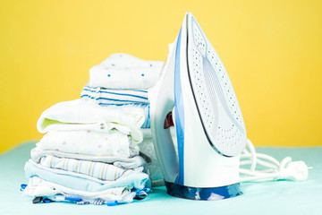 newborn baby clothes and accessories ready to be ironed, with an electric steam iron on happy yellow background