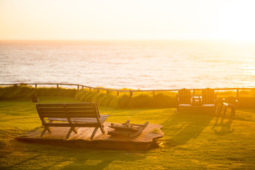 Wooden bench on cute platform overlooking the Pacific Ocean at sunset in Big Sur, California.