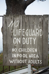 No lifeguard wooden sign at a pool in Big Sur.