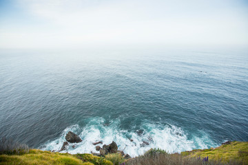 Blue water of the Pacific ocean crashing onto the rocky shores below the cliffs in Big Sur, California.