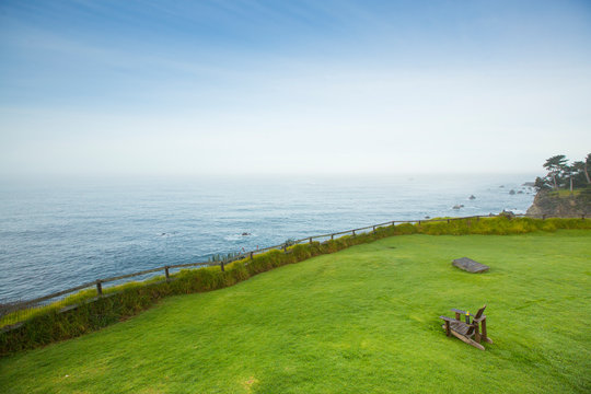 An expanse of soft green grass with a wooden chair looking out to the Pacific Ocean in Big Sur, California.
