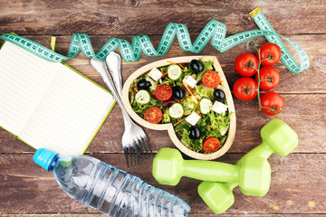 Authentic fresh salad in a wooden heart shaped cup with dumbbells excercise equipment, measuring...