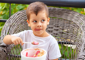 little boy with a spoon eating ice cream