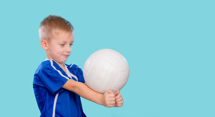 Happy little kid in a blue shirt with a ball for volleyball. Physical, sport.