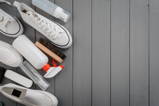 Different shoes and cleaning supplies on gray wooden background