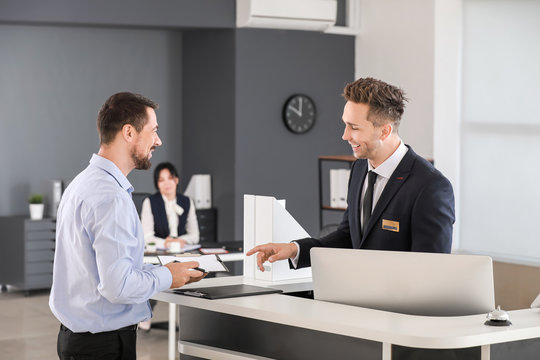 Male receptionist working with visitor in office
