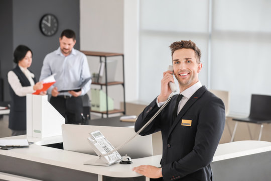 Male receptionist talking on phone in office