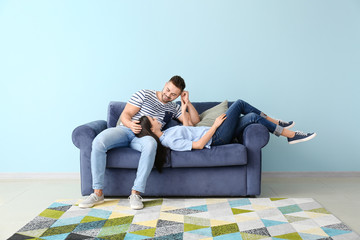 Young couple resting on sofa at home