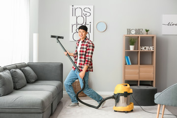 Young Asian man having fun while cleaning floor at home