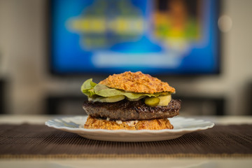 LCHF Low carbohydrate high fat burger or hamburger meal. LCHF burger with non carbohydrate bread made of sesame, eggs, chees, almonds. Concept picture of a LCHF burger in front of television screen.
