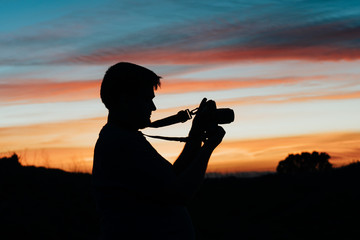 A man taking pictures with his analog camera in a sunset at golden hour