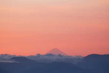 Silhouettes of mountains with clouds and volcano in the background - A view of the volcanoes of Guatemala - Sunset between mountains