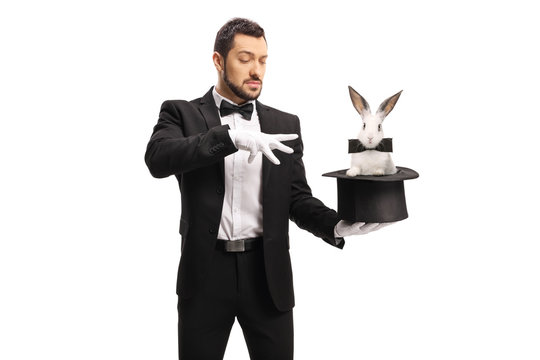 Young male magician making a magic trick with a rabbit in a top hat
