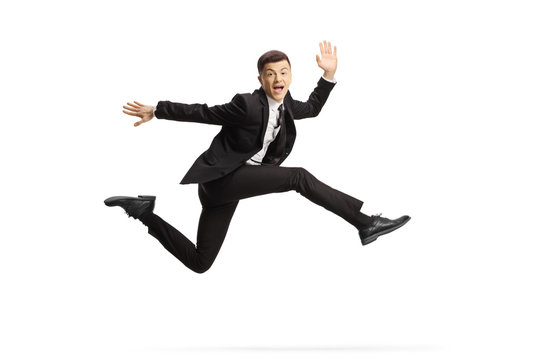 Cheerful young man in a black suit jumping and looking at camera