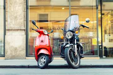 Tuinposter Scooter Vintage red scooter and black motorcycle parked on road empty italian city street. Symbol of couple, love, relations of man and woman. Advenure and travel lifestyle. Italian culture scenic background