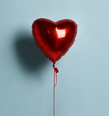 Metallic foil single red heart balloon object for birthday party or valentines day on pastel color light blue