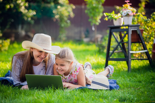 Woman and little girl laying on the spring flower field outdoors - having fun using a laptop