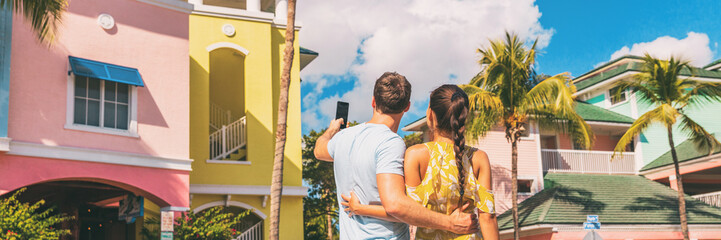 Couple on winter vacation taking pictures of pastel colored beach houses cottages in tropical holiday destination Fort Myers, Florida. Man tourist taking picture with phone.
