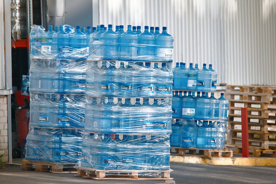 Minsk, Belarus. Oct 2019. Plastic bottles of purified drinking water on pallets. Water production, gallons of pure water at warehouse. Bottled water prepared for delivery. Stacks plastic bottles