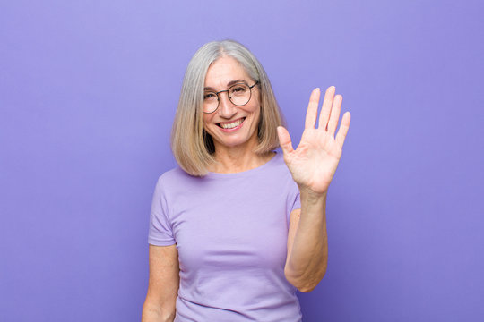 senior or middle age pretty woman smiling happily and cheerfully, waving hand, welcoming and greeting you, or saying goodbye