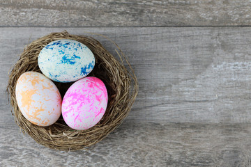 Group three colorful and decorated easter eggs in bird nest on vintage wooden background. Advertising image Easter or food concept with free space.