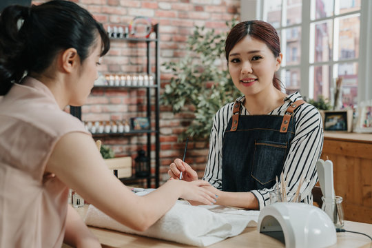 Beautiful girl manicurist doing manicure for young office lady in beauty salon. confident beautician face camera smiling while working and painting nail polish on client nails with brush in workshop.