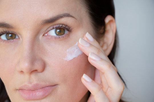 woman applies wrinkle cream on lower eyelid