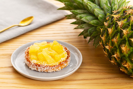 Small pineapple tart or tartlet with glazed pineapple fruit pieces and grated coconut by an entire pineapple fruit and a grey napkin with a golden spoon, all over a light oak wooden background.