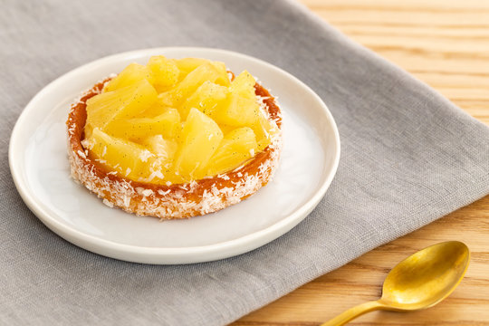 Small pineapple tart or tartlet with glazed pineapple fruit pieces and grated coconut on grey napkin by a golden spoon, over a wooden background.