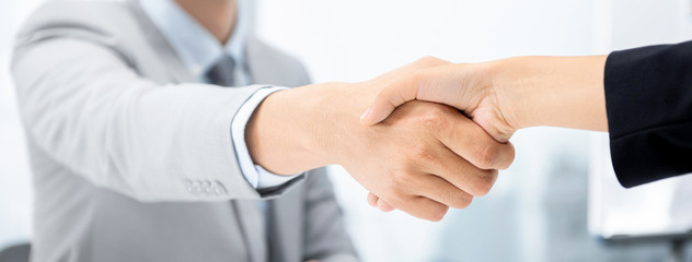 Businesspeople making handshake at meeting room on banner background