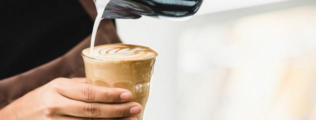 Professional barista making latte art coffee