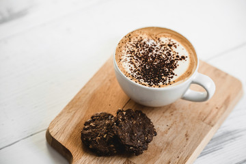 Hot latte coffee in the cup with chocolate cookies