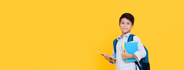 Handsome schoolboy with backpack holding books and tablet computer on banner background