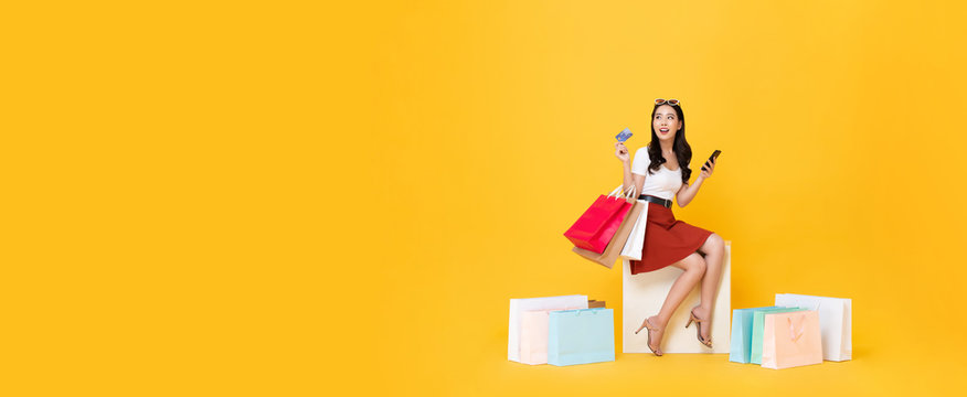 Woman carrying shopping bags with credit card on banner background